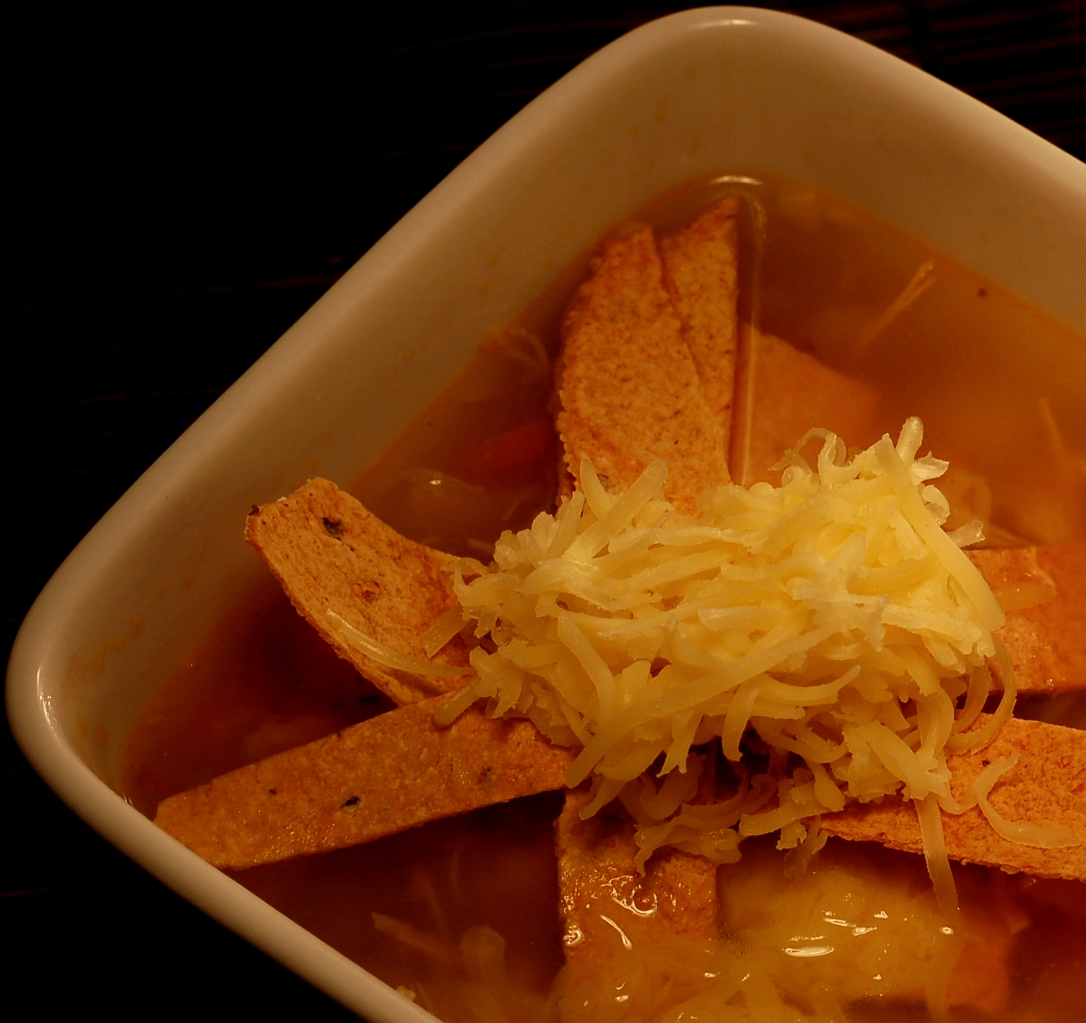 cooking, culinary, recipes, food and wine, food and drink, dinner, soup, peppers, mexican, latin, spanish, food blog, Warm and spicy chicken chipotle soup topped off with baked tortillas and cheddar cheese.